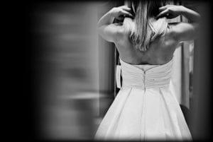 Une femme essaye une robe de mariée.