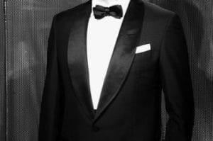 Smoking noir sur chemise blanche.