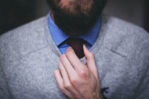 Gros plan sur le col d'un homme, en chemise, pull et cravatte.